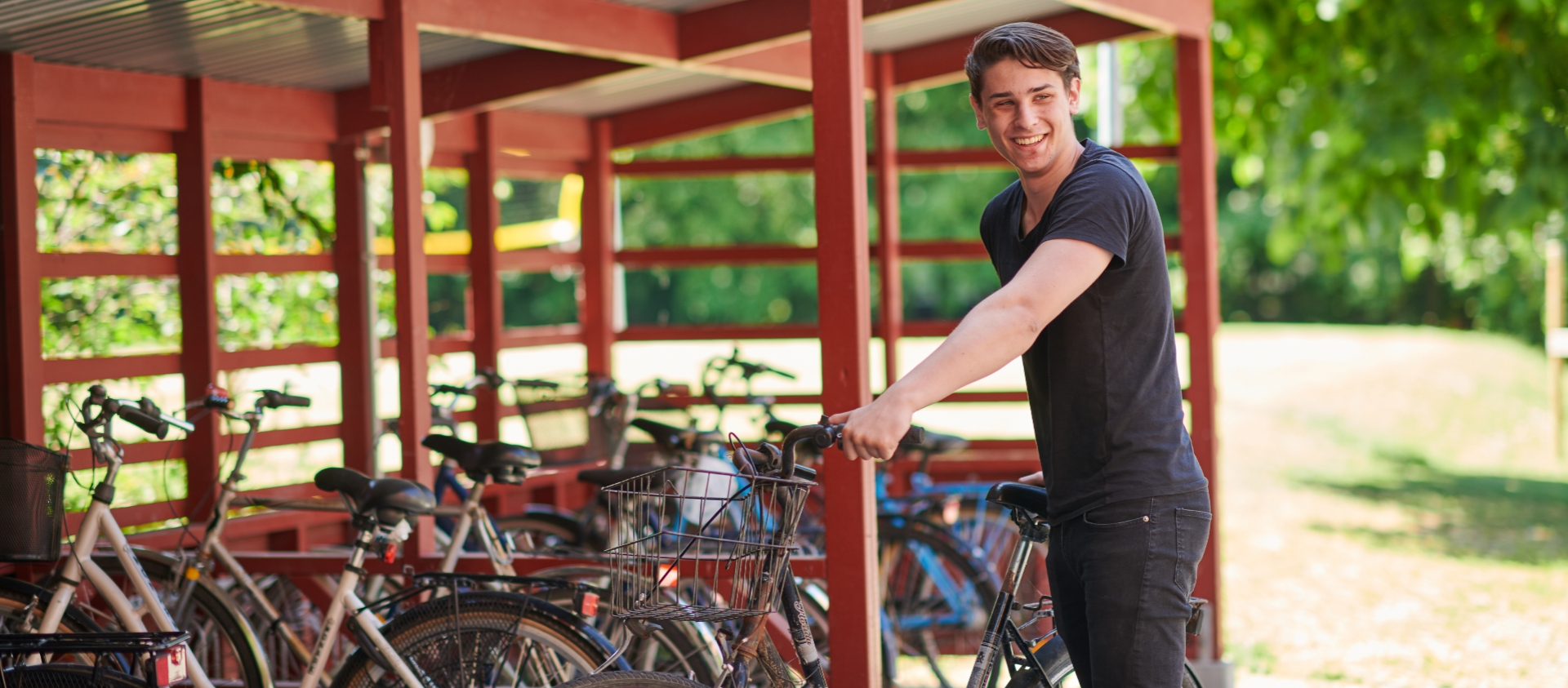 Male student with bike in front of bike parking with roof